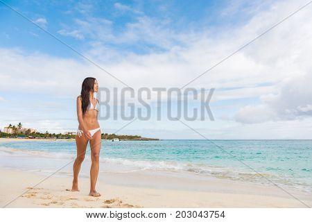 St Maarten beach bikini woman on cruise ship vacation travel walking relaxing in famous touristic destination. Asian girl full length body.