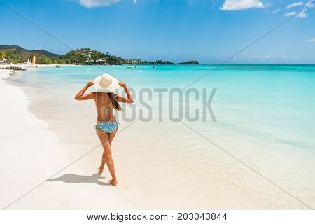 Antigua beach woman on cruise vacation travel in Caribbean island. Bikini girl walking on white sand wearing sun hat relaxing on idyllic paradise tourist attraction.
