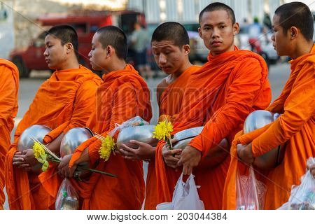 CHIANG MAI THAILAND - 1/8/2016: Young monks collect donations in Chiang Mai Thailand.