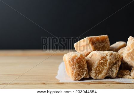 Fudge Pieces On Light Wood Table With Black Background