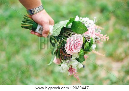 Groom holding pink wedding bouquet. Marriage concept selective focus. Marriage concept