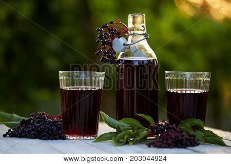 Glasses Of Fresh Elderberry Syrup And Elderberries