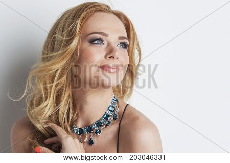 Portrait of beautiful woman with blonde curly hair and necklace of blue precious stones close up