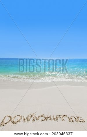 Downshifting text on white sandy beach and sea