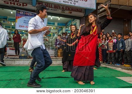 POKHARA NEPAL - 11/9/2015: A group of young Nepalese dancers perform in traditional clothes during the Tihar festival in Pokhara Nepal.