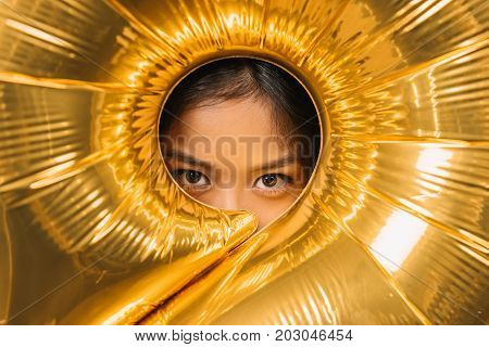 obscured view of woman looking at camera through balloon