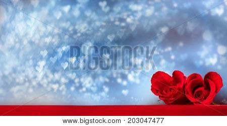 Two heart shaped red roses on glowing bokeh lights background