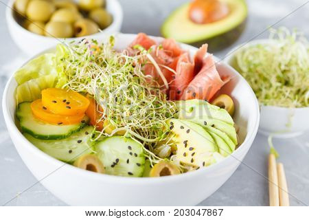 Hawaiian fish poke with rice avocado and sprouts.