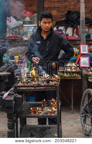 KATHMANDU NEPAL - 9/26/2015: A candle salesman smokes a cigarette at Durbar Square during the Indra Jatra festival in Kathmandu Nepal.