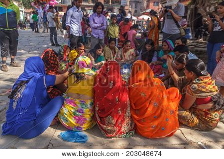 KATHMANDU NEPAL - 9/26/2015: A group of Hindu women in traditional sari sit at Durbar Square in Kathmandu Nepal.