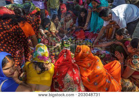 KATHMANDU NEPAL - 9/26/2015: Hindu women in traditional sari sit together during Indra Jatra at Durbar Square in Kathmandu Nepal.