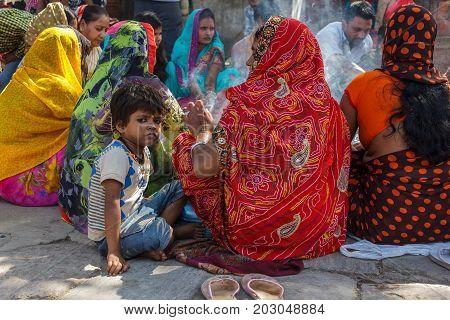 KATHMANDU NEPAL - 9/26/2015: A boy sits with Hindu women in traditional sari at Durbar Square in Kathmandu Nepal.