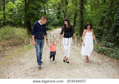 Family With One Girl Child Walk In Park With Grandmother