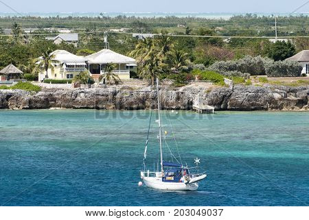 The yacht drifting by the Grand Cayman island shore (Cayman Islands).