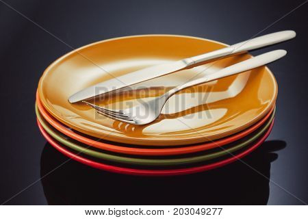 knife, fork and plate at glossy black background