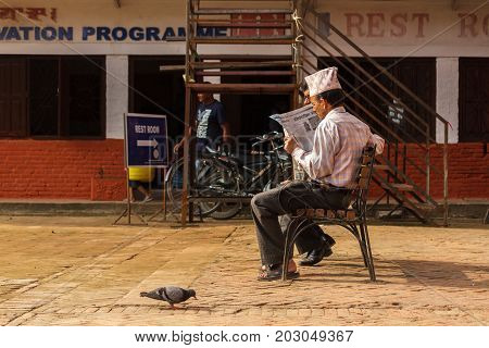 KATHMANDU NEPAL - 9/26/2015: A Nepalese man reads a newspaper on a bench near Durbar Square in Kathmandu Nepal.