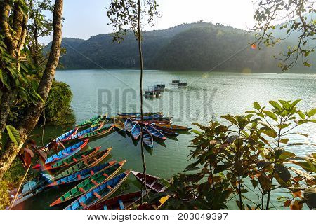 Colorful canoe boats at sunrise on Phewa Lake in Pokhara Nepal.
