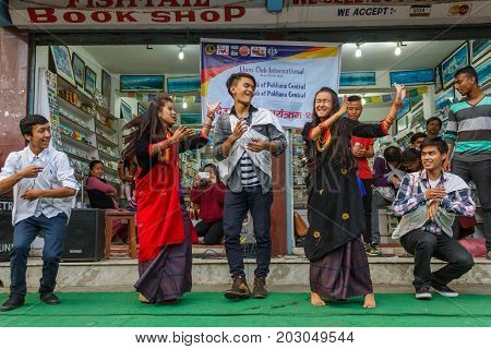 POKHARA NEPAL - 11/9/2015: A group of young Nepalese performers laugh and dance in traditional clothes during the Tihar festival in Pokhara Nepal.