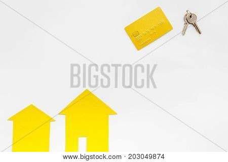work desk with keys, credit card and paper house figures for selling house set white background top view space for text