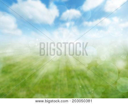 Blurred green meadow and blue sky spring background