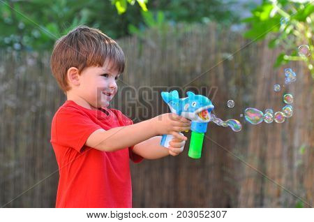 Boy make a soap bubbles. Boy play in the yard with soap bubbles