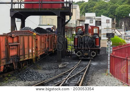 Porthmadog Wales UK - September 4 2017: Narrow gauge steam locomotive David Lloyd George of the Ffestiniog Railway Company being filled with coal at a coaling station in Porthmadog