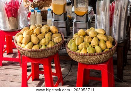 Street market. Ripe yellow mangoes in wicker baskets on the street mango juice and cocktails.