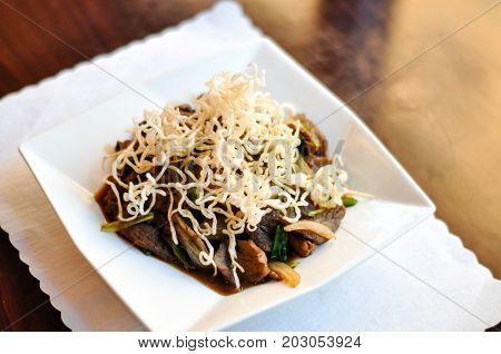 Stir-Fried Mongolian Beef, Stir-fried beef with green and white onion in a special sauce and topped with crispy rice noodles