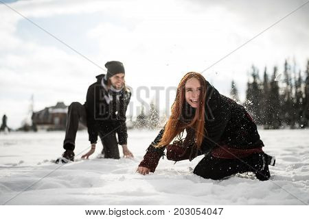 Carefree happy couple having fun together in snow