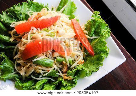 Papaya Salad, Shredded green papaya, tomatoes, green beans, crushed peanut & lime dressing