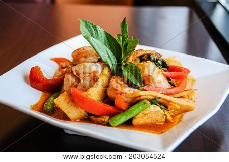 Stir-Fried Spicy Seafood, Stir-fried red curry with shrimp, mussels, scallops, squids, crabmeat, fish balls, bamboo shoots, green beans, basil leaves and eggplant