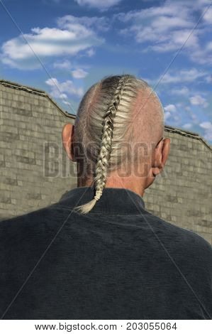 Masculine Hairstyle. Rear view of the back of a man's head and shoulders against a blue sky. Blond hair braided in a pigtail.