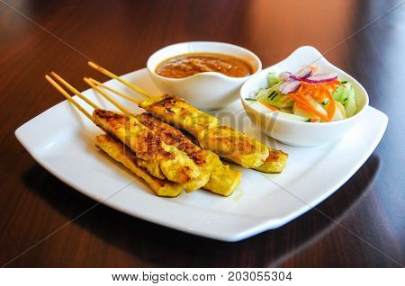 Chicken Satay, Marinated chicken grilled on skewers, served with peanut sauce and cucumber salad