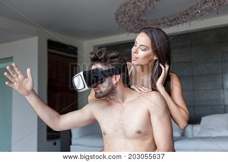 Couple playing with VR glasses at home virtual reality man touching in cyberspace