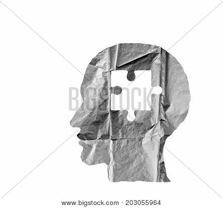 Crumpled paper shaped as a human head and puzzle on white background. Puzzle concept.
