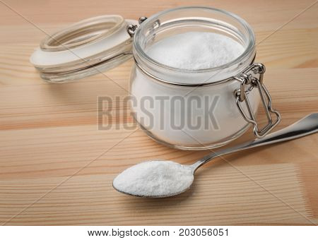 Jar and spoon of baking soda poster