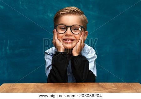 Happy smiling caucasian child sitting at workplace and imitating office worker. Portrait of cute boy wearing eyeglasses and shirt looking at the camera.