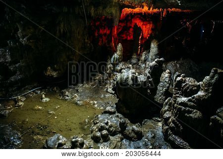 Stalagmites inside a large underground cave, wet cave with water on the floor