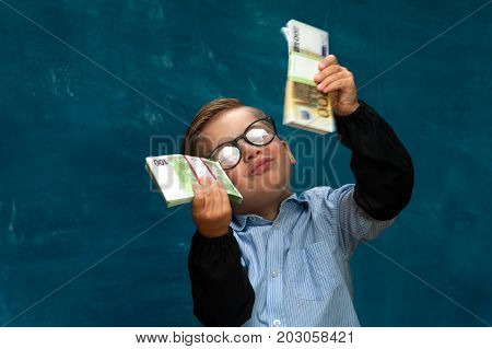 Happy smiling child wearing eyeglasses with cash in hands. Little boy posing on blue backdrop, imitating successful businessperson