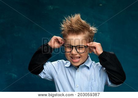 Funny little boy wearing eyeglasses and shirt sitting at workplace and imitating crazy office worker. Portrait of smiling cute boy posing on blue backdrop and looking at the camera