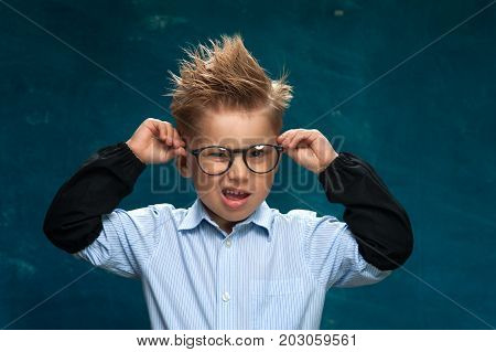 Crazy little boy wearing eyeglasses and shirt with tousled hair posing on blue backdrop, imitating office worker.