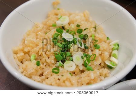 Homemade garlic fried rice with mixture vegetables (spring onion on top rice) serve on bowl for japanese food background or texture.