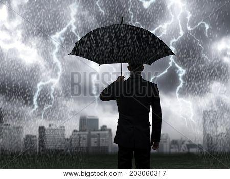 Businessman hold black umbrella standing under rain storm lightning with city background