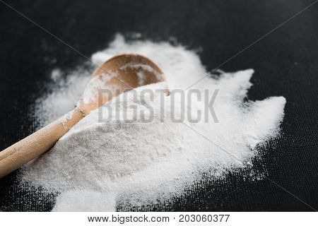 Spoonful of bicarbonate. Baking soda Sodium bicarbonate NaHCO3. wooden spoon on a black background.