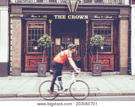 London, March 2017 UK: Urban scene of a cyclist walking in front of an English pub, Blurred motion of the cyclist by the motion effect over the pub on the static background