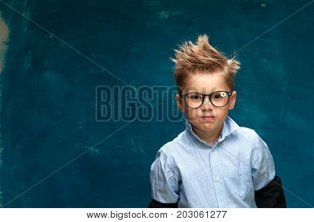 Funny portrait of caucasian child wearing eyeglasses and shirt imitating businessperson or office worker. Little boy crossing his arms on chest, looking at the camera. Copyspace