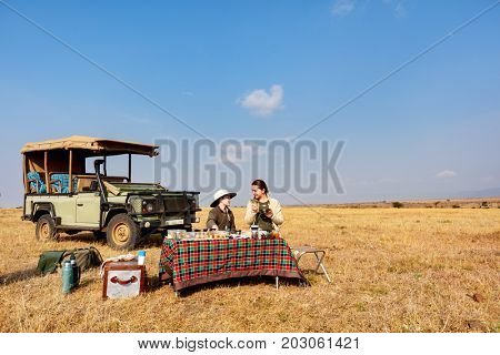 Family of mother and her son on African safari vacation enjoying bush breakfast