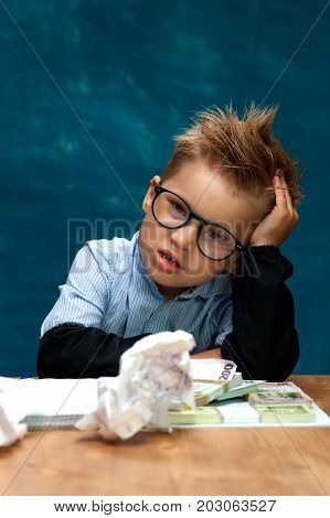 Cute stylish boy wearing eyeglasses sitting at workplace with cash and crumpled papers. Portrait of tired child imitating businessperson or bookkeeper.