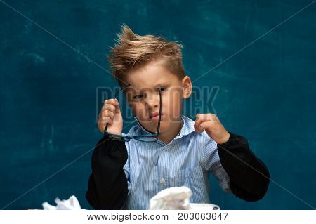 Tired depressed child sitting at workplace imitating businessperson or office worker. Stylish boy sitting at workplace with crumpled papers and documents.