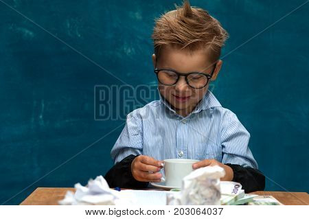 Smiling little boy wearing eyeglasses imitating businessman or bookkeeper. Cute caucasian child sitting at the workplace with crumpled papers and drinking coffee.